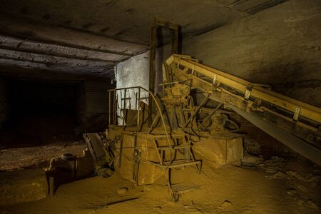 Abandoned limestone mine. Old rusty stone cracking and loading equipment with conveyor belt.