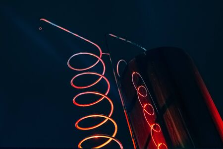 Vat and metallic spiral of alcohol machine red illuminated.