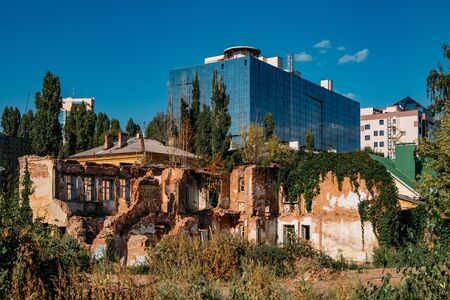 Old abandoned overgrown ruined house on modern building   background, Voronezh, Russia. Contrast and time concept.