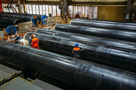Workers examine new coated pipe in factory. Stock fotó
