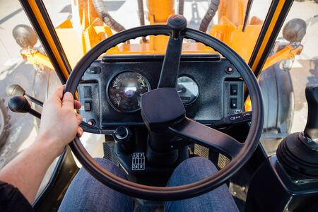 Inside modern tractor. Steering wheel. View from work place.