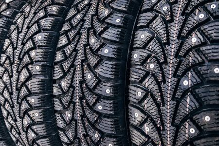 Clean new modern studded winter tires in row. Tires with spikes, close up. Banco de Imagens