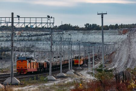 Freight train with ore in open mining quarry.