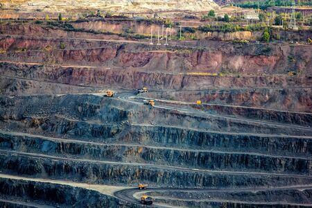 Open mining quarry. Dump mining trucks with ore.