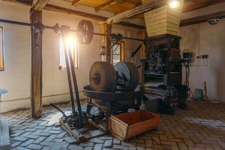 Ancien moulin à huile, meules et presse mécanique. Banque d'images