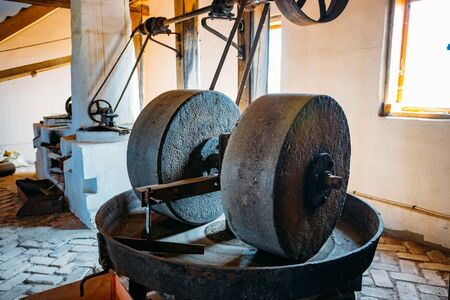 Old oil mill, millstones and and mechanical press. Stok Fotoğraf