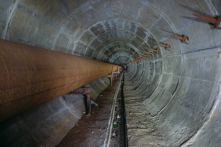 Old round dirty underground tunnel of heating duct with rusty pipeline