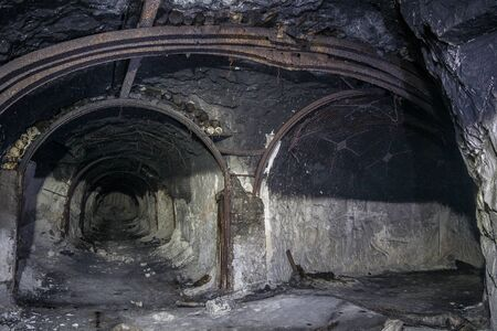 Entrance to abandoned chalk mine. Metal mine roof supports, fork in the tunnel