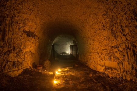 Abandoned chalk mine tunnel with traces of drilling machine and remnant of equipment, illuminated by candles, Belgorod, Russia