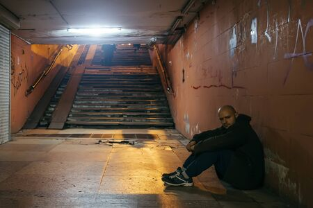Depressive sad man sitting in on ground of street subway tunnel. Despair concept.