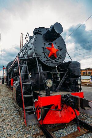 Old black steam locomotive on railway station.