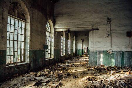 Antiguo edificio abandonado con ventanas lancetas rotas en el interior.