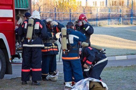 Group of firemen putting on gas masks and preparing for extinguish fire. Stok Fotoğraf