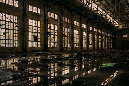 Dark dirty flooded dirty abandoned ruined industrial building with water reflections at night Stok Fotoğraf