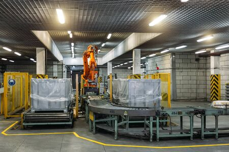 Robot Hand manipulator packaging factory products from conveyor into container.