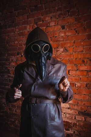 Terrible plague doctor on red brick background. Masked maniac with scalpel and scissors. Halloween and horror