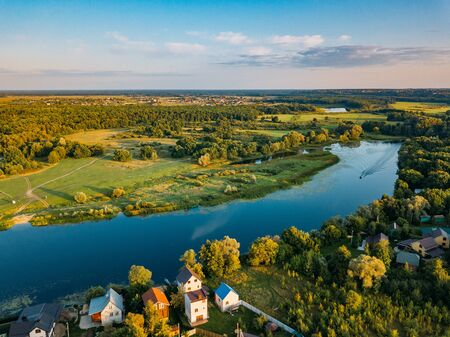 Summer rural landscape, aerial view. Village, forest and river from drone flight.