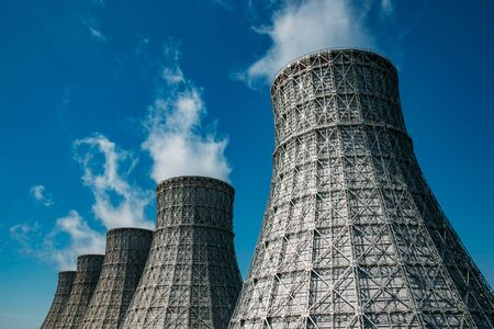 Cooling tower of nuclear power plant against blue sky.