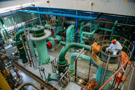 Worker repairs pipeline of water circulation in power plant.