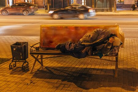 Unknown homeless or alcoholic or drug addict are sleeping on the bench at night. Stock fotó