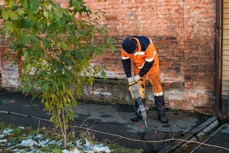 Road worker drilling asphalt on pavement with jackhammer.