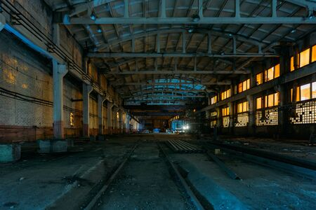 Old broken empty abandoned industrial building interior at night. Banque d'images