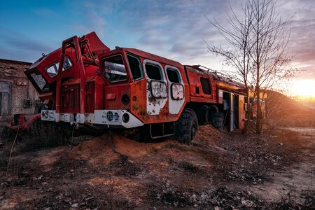 Old rusty broken abandoned Soviet fire truck on evening sunset.