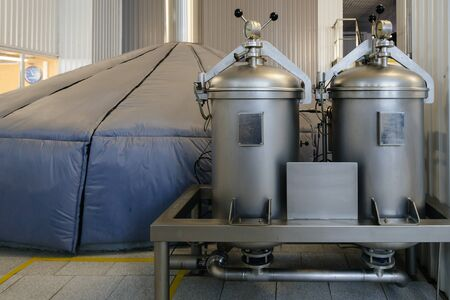 Vats for mash fermentation and cylinders with gas in and hop dispenser in modern brewery.
