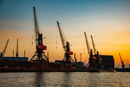 Harbor cargo cranes on sunset sky background.