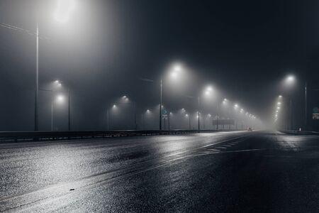 Strada di notte nebbiosa nebbiosa illuminata da lampioni. Archivio Fotografico