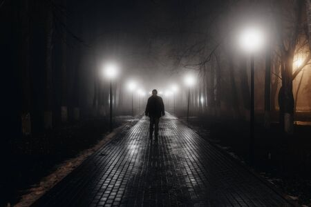 Sad man alone walking along the alley in night foggy park. Back view 스톡 콘텐츠