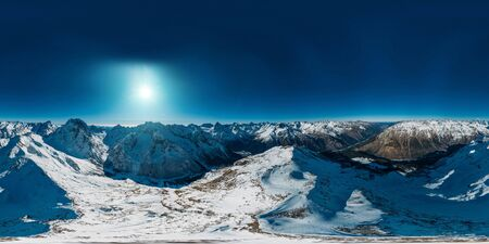 Panoramic 360 degree aerial drone view of snowy mountains.