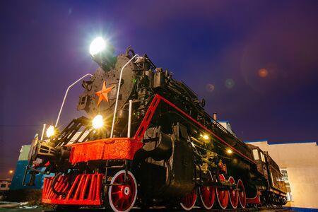 Old black steam locomotive on railway station at night. Standard-Bild