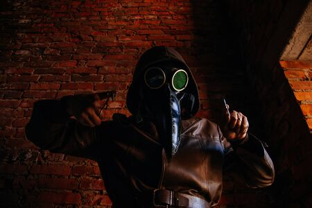 Terrible plague doctor on red brick background. Masked maniac with scalpel and scissors. Halloween and horror. Zdjęcie Seryjne