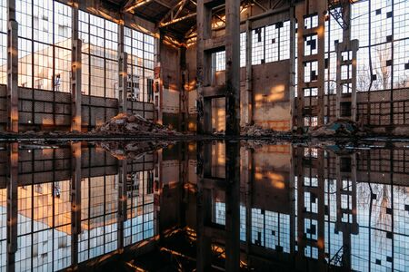 Inside of flooded dirty abandoned ruined industrial building with water reflection.