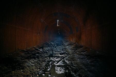 Dark dirty flooded abandoned vaulted mine tunnel. Stock Photo