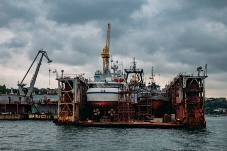 Ships in floating dry dock under repair. Stock Photo