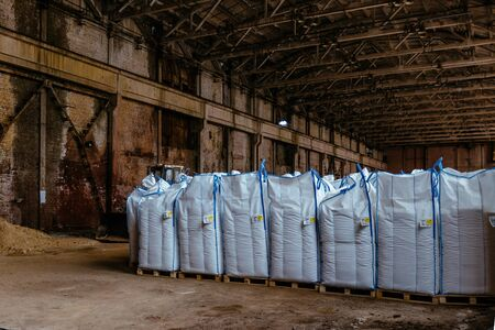 White polyethylene bags with factory products in warehouse.