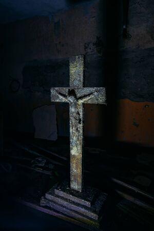Old rotten wooden statue of crucified Jesus Christ in dark room.