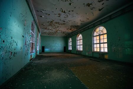 Large empty hall inside old abandoned building.