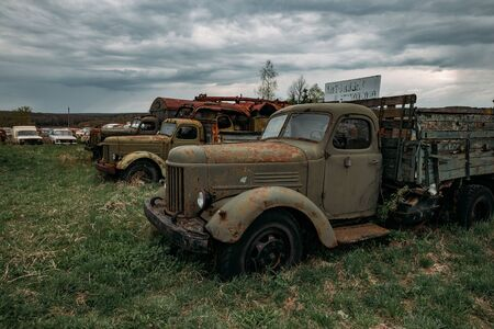 Old rusty truck at abandoned overgrown industrial area.