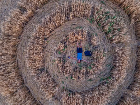 Happy man on crop circle in oat field, aerial view.