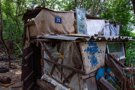 Homeless dweling. Small habitation made from garbage in dirty littered forest.