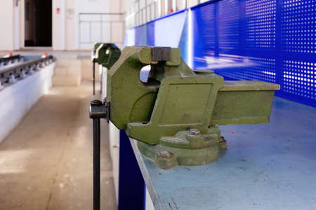 Green steel vice in the metalworking workshop. Archivio Fotografico
