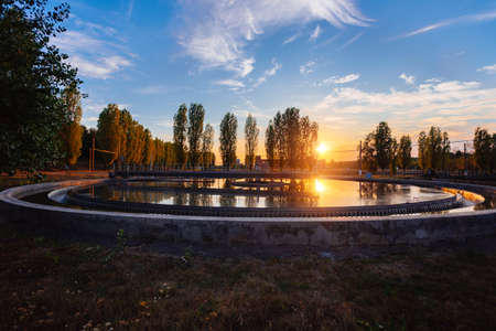 Modern sewage treatment plant. Round wastewater purification tank at sunset.