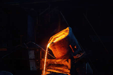 Metal casting process in metallurgical plant.Liquid metal pouring into molds.