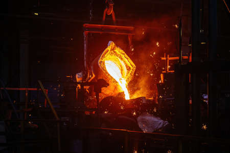 Metal casting process in metallurgical plant. Liquid metal pouring into molds.
