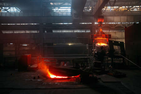 Worker operates metal casting process in metallurgical plant. Reklamní fotografie
