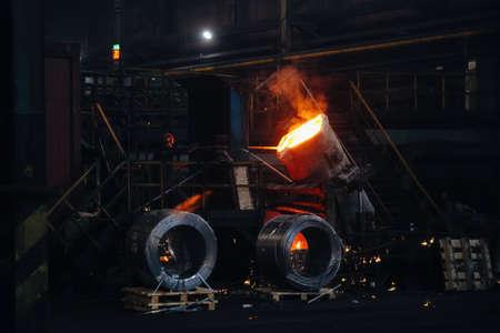 Worker operates metal casting process in metallurgical plant. Zdjęcie Seryjne