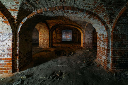 Dark and creepy vaulted red brick dungeon.
